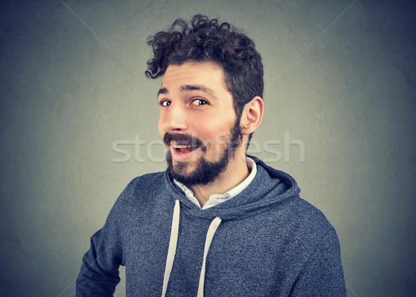 Sluw jonge man naar camera glimlach gezicht Stockfoto © ichiosea