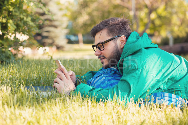 Chilling hipster in park with smartphone Stock photo © ichiosea