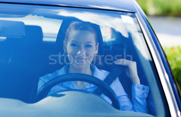 Woman pulling on seatbelt inside black car Stock photo © ichiosea
