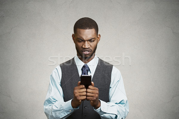 Angry executive holding smart phone, reading e-mail Stock photo © ichiosea