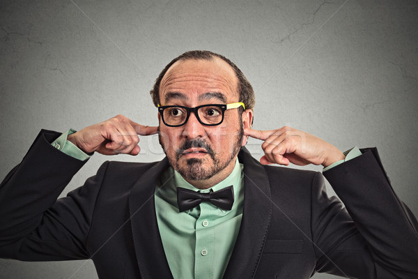 Annoyed mature man with glasses plugging ears with fingers Stock photo © ichiosea