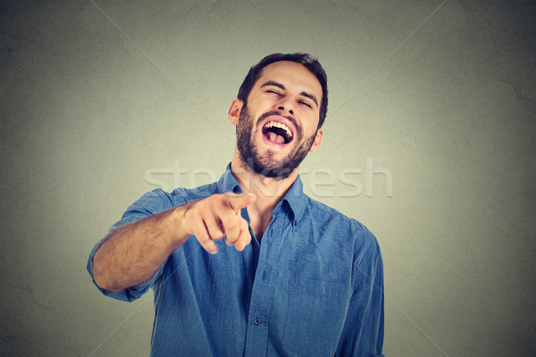 Laughing young guy pointing with finger at camera  Stock photo © ichiosea