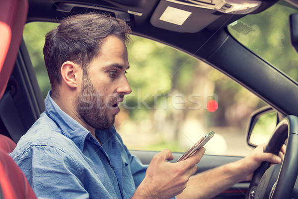 Stock photo: Man sitting in car with mobile phone in hand texting while driving