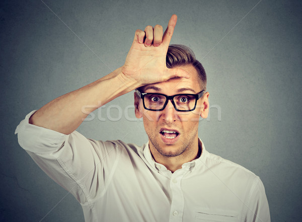 young man in glasses showing loser sign on forehead Stock photo © ichiosea