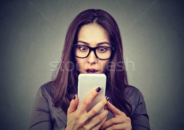 Shocked woman looking at mobile phone Stock photo © ichiosea