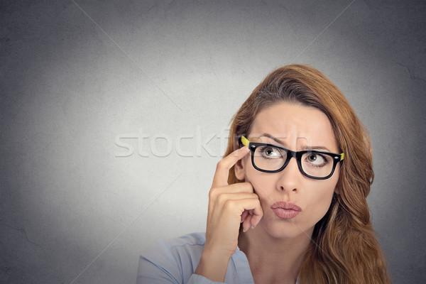 Nadenkend jonge vrouw bril naar verward geïsoleerd Stockfoto © ichiosea