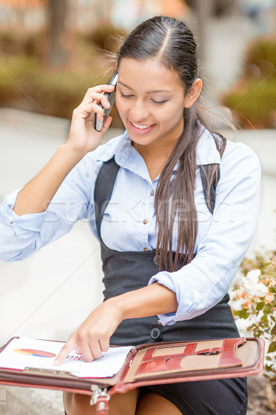 businesswoman sitting outside reviewing financial statements paperwork talking on mobile phone Stock photo © ichiosea