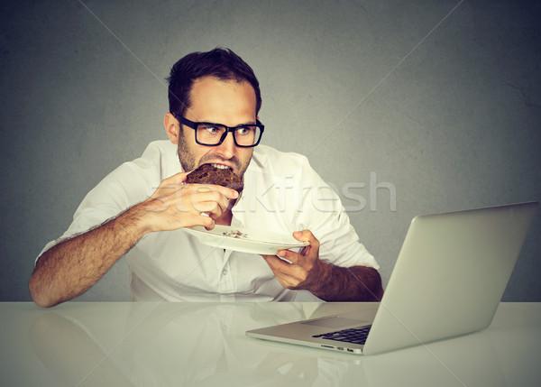 Jovem estudante homem alimentação trabalhando laptop Foto stock © ichiosea