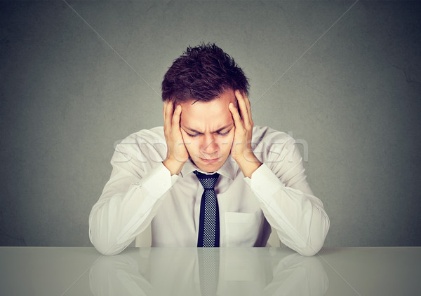 Desperate sad young businessman leaning on a desk Stock photo © ichiosea
