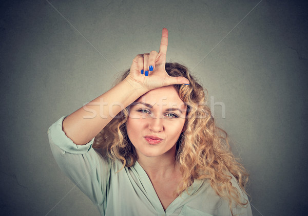 young unhappy woman giving loser sign on forehead Stock photo © ichiosea