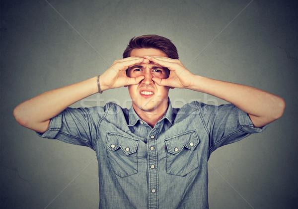 Niezadowolony młody człowiek patrząc palce jak lornetki Zdjęcia stock © ichiosea