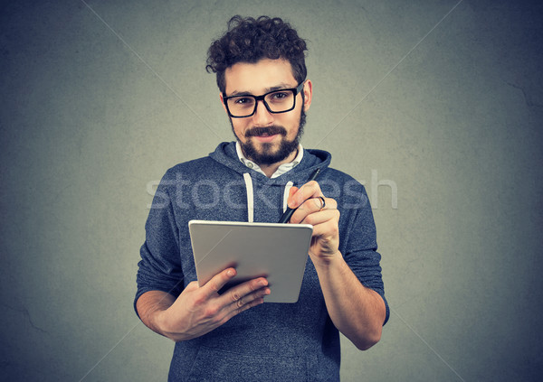 Hispter man in glasses holding tablet computer and pen looking at camera Stock photo © ichiosea