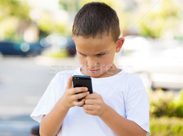 Unhappy boy looking at his smart phone Stock photo © ichiosea