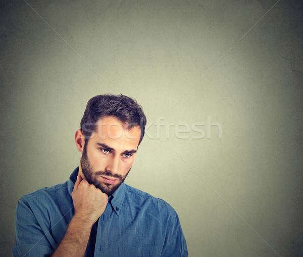 Sad depressed young man holding head with hand looking down Stock photo © ichiosea