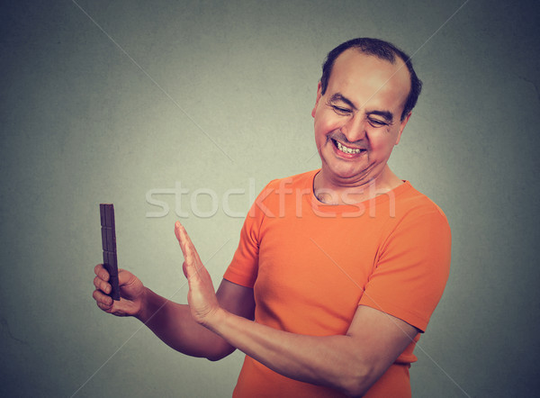 Dieting man. Confused man trying to withstand, resist temptation to eat chocolate  Stock photo © ichiosea