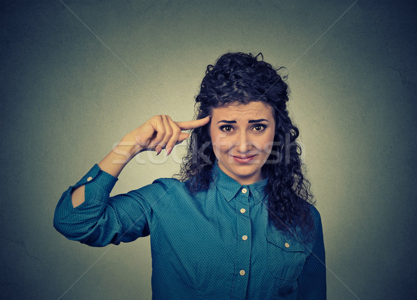 annoyed woman gesturing with her finger against temple asking are you crazy? Stock photo © ichiosea