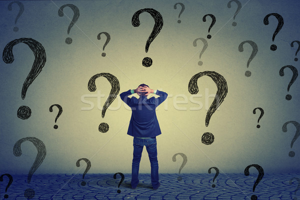 Rear view business man standing in front of wall with many questions Stock photo © ichiosea