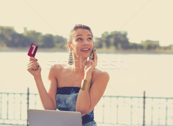 Woman talking on mobile phone holding credit card and laptop  Stock photo © ichiosea