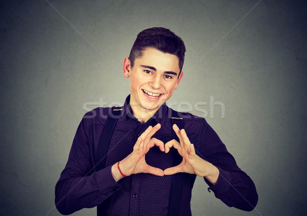 Knap glimlachend jonge man hartvorm vingers handen Stockfoto © ichiosea