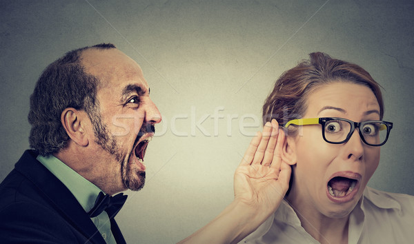 angry man screaming curious woman with hand to ear gesture listens Stock photo © ichiosea