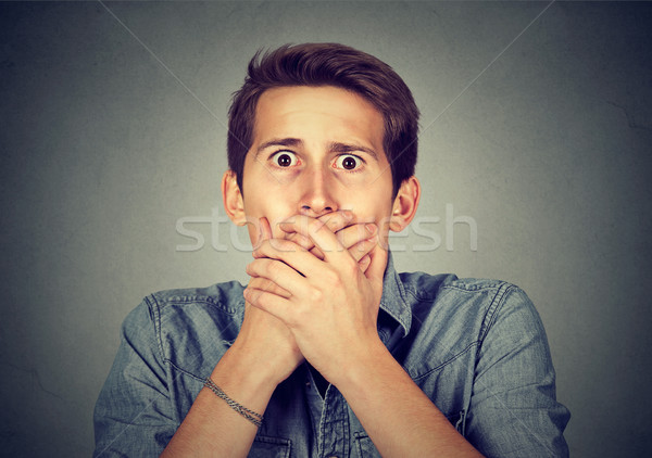 shocked young man covering his mouth with hands Stock photo © ichiosea