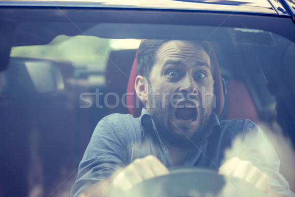 Man driving a car shocked about to have traffic accident, windshield view  Stock photo © ichiosea