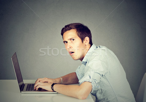 Surprised man with laptop sitting at desk   Stock photo © ichiosea