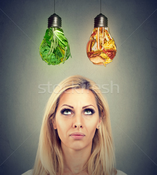 Woman thinking making a diet choice looking up at junk food and green vegetables shaped as light bul Stock photo © ichiosea