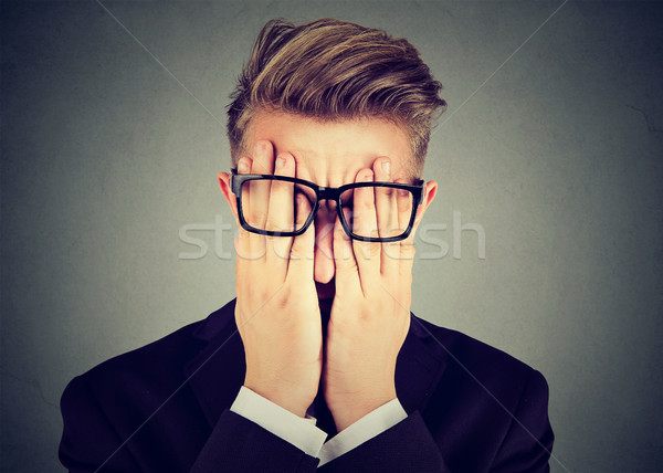 Closeup portrait young man in glasses covering face eyes with both hands Stock photo © ichiosea