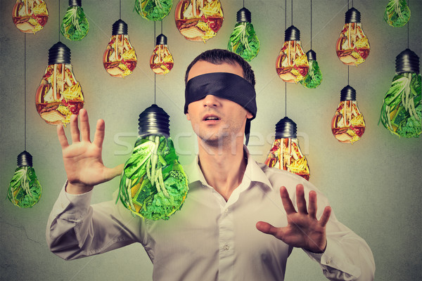 Blindfolded man walking through light bulbs shaped as junk food green vegetables Stock photo © ichiosea