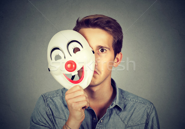 Young sad man hiding behind happy clown mask  Stock photo © ichiosea