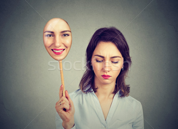 Sad young woman looking down taking off happy mask of herself  Stock photo © ichiosea
