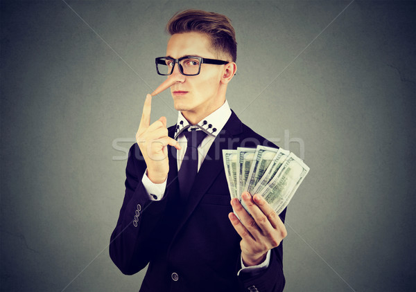 Financial fraud concept. Liar business man in suit and glasses with dollar cash  Stock photo © ichiosea