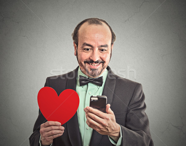 man checking his smart phone, holding red heart  Stock photo © ichiosea