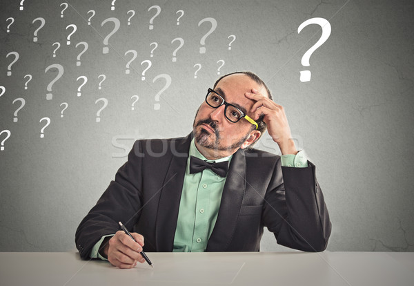 puzzled business man sitting at table scratching his head thinking Stock photo © ichiosea