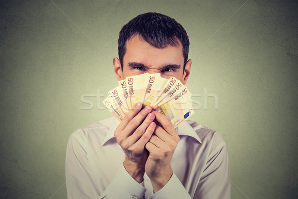 Greedy man with euro banknotes bills isolated on gray wall background   Stock photo © ichiosea