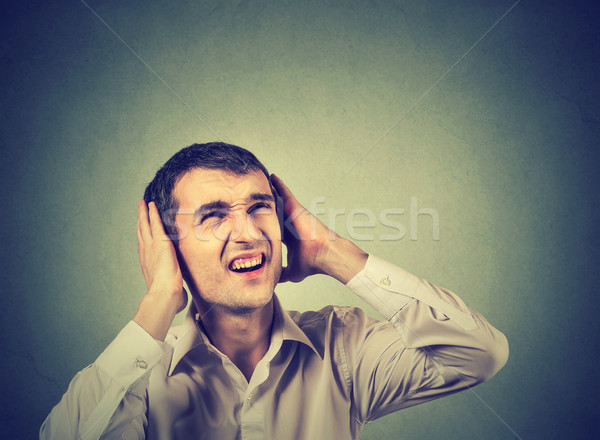 annoyed stressed man covering ears, looking up, stop making loud noise Stock photo © ichiosea