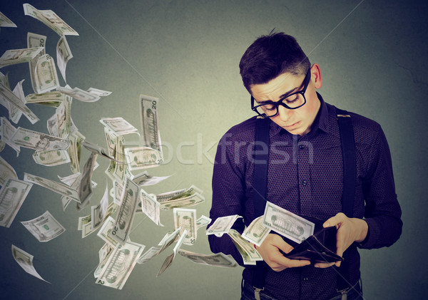Sad man looking at wallet with money dollar banknotes flying away  Stock photo © ichiosea