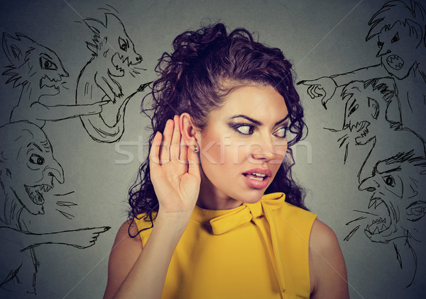 woman holds her hand near ear and listens carefully to evil voices  Stock photo © ichiosea