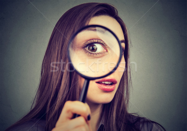 Curious woman looking through a magnifying glass  Stock photo © ichiosea