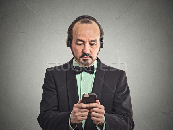 man listening to music on smartphone with pair of headphones Stock photo © ichiosea