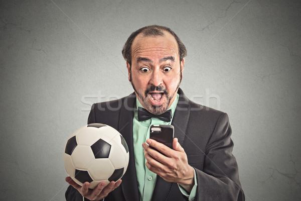Man watching football game on smart phone Stock photo © ichiosea