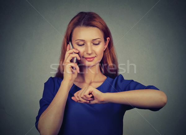 Woman talking on mobile phone looking at her wrist watch  Stock photo © ichiosea