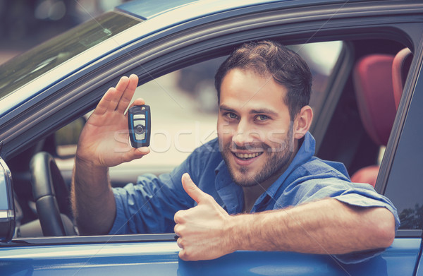 Happy man sitting in new car showing keys thumbs up Stock photo © ichiosea