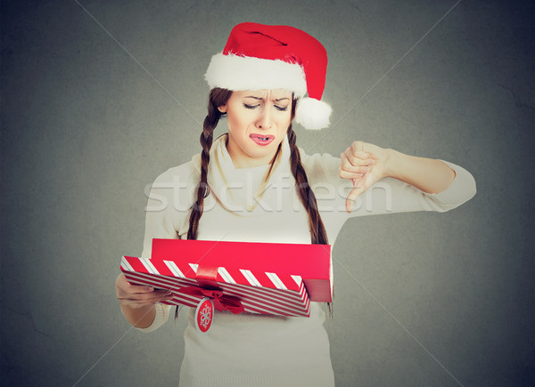 woman in santa claus hat opening gift upset showing thumbs down  Stock photo © ichiosea