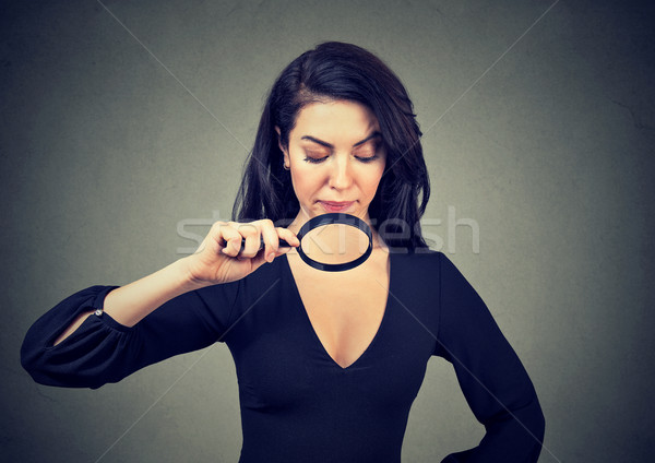 Young woman looking at her breasts through magnifying glass  Stock photo © ichiosea