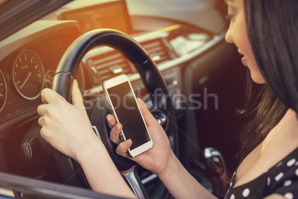 Woman looking at her smartphone while driving a car on a sunny day  Stock photo © ichiosea