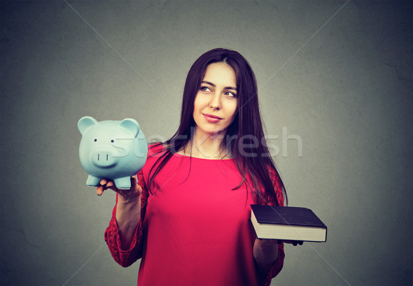 Cost of college education. Thoughtful woman balancing piggy bank and book Stock photo © ichiosea