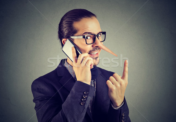Stock photo: Sly liar business man with long nose talking on mobile phone