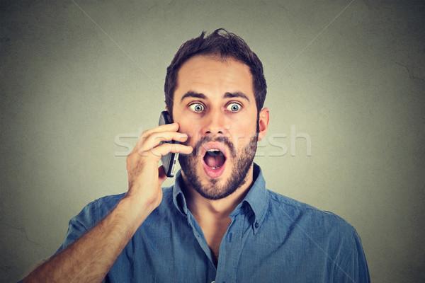 Shocked man talking on mobile phone  Stock photo © ichiosea